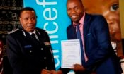Isaac Magagula handing a certificate to a police officer